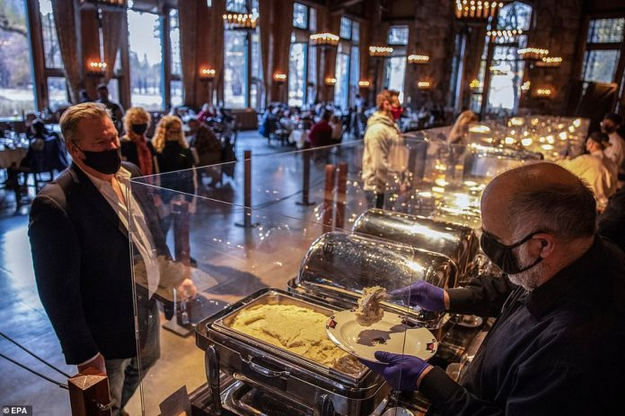 Yosemite Valley, California: Thanksgiving day visitors stand in line at a touch-less dinner buffet in Ahwahnee Dining Room in Yosemite Valley National Park on Thursday