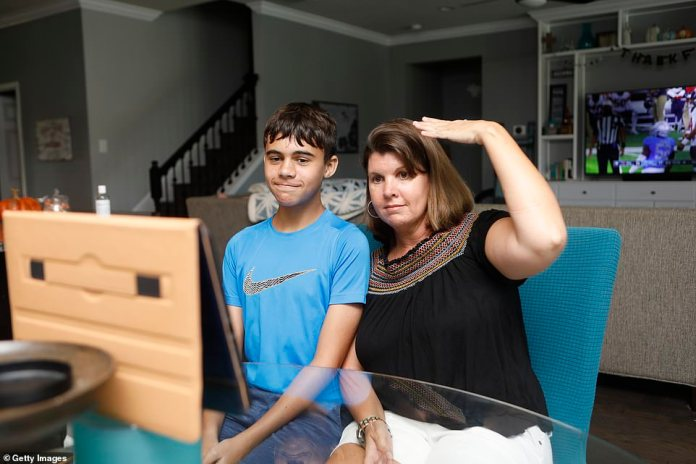 Valrico, Florida: Jennifer Collis and her youngest son Timmy talk with family members in Delaware and Ohio on a Zoom call on Thanksgiving Day