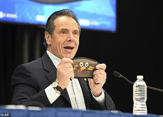 Cuomo holds up a new Thanksgiving-themed face mask during his daily coronavirus briefing at the Wyandanch-Wheatley Heights Ambulance Corp