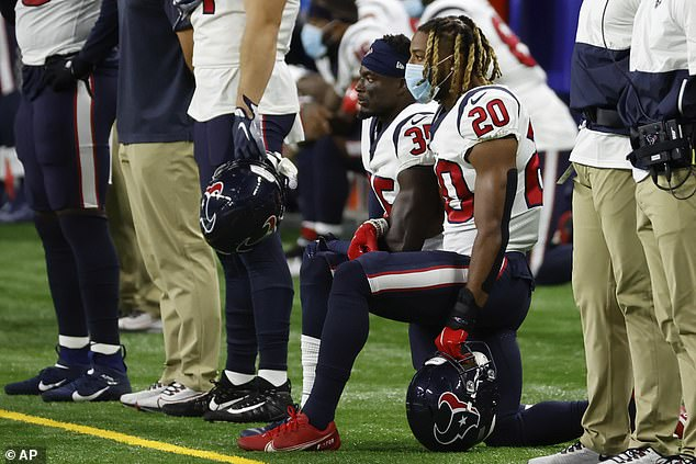 Houston Texans cornerback Keion Crossen, number 35, and strong safety Justin Reid, number 20, kneel during the national anthem prior to an NFL football game against the Detroit Lions yesterday in Detroit