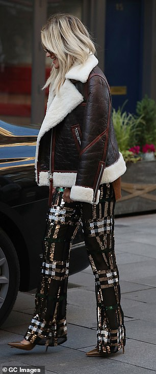 Cosy: The 39-year-old made sure to combat the chilly London temperatures by draping a shearling lined aviator jacket over her shoulders