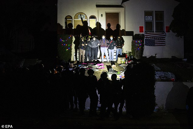 Activists reclaiming the Caltrans homes face off with CHP officers on Thanksgiving night in El Sereno, Los Angeles