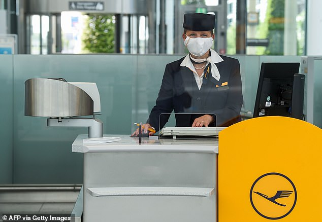 Lufthansa's announcement comes as airlines plan to make travellers feel safe enough to fly again following positive news of coronavirus vaccine developments in the USA and UK. Pictured: A member of the Lufthansa ground crew at Franz-Josef-Strauss Airport in Munich [File photo]