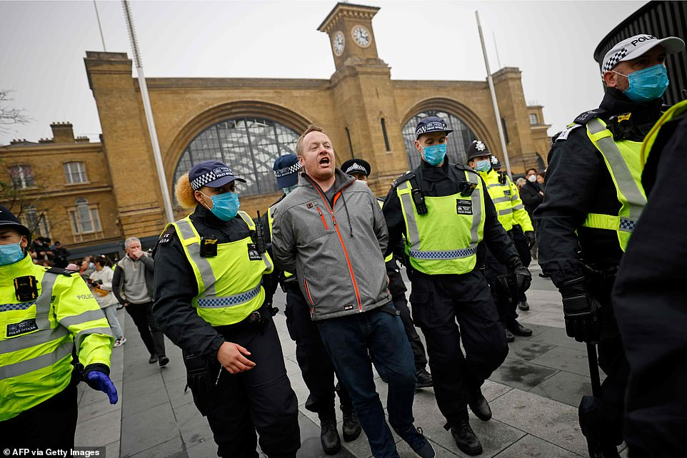 Police officers take away a protester ahead of an anti-lockdown protest at King's Cross station
