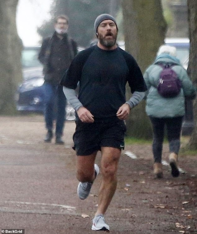 Muscle man: Undeterred by the inclement winter weather, the screen star displayed his enviably muscular legs in a pair of black shorts, which he teamed with a matching top