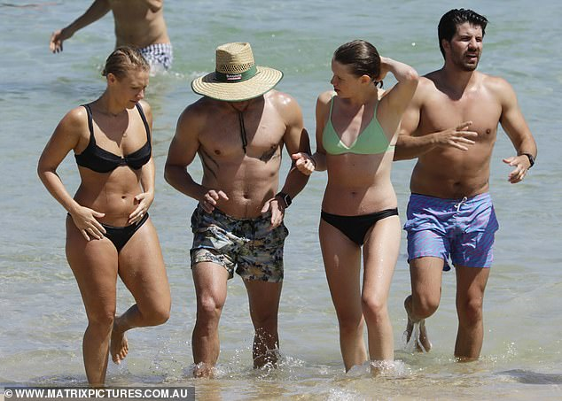 Time to cool down! After spending some time chatting on the sand, Luke and his friends headed to the shallows for a dip