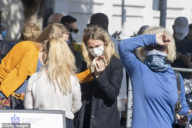 People are seen talking as they line up at a pop-up COVID-19 testing clinic in Rushcutters Bay in Sydney (pictured) with free testing available to all Australians since March