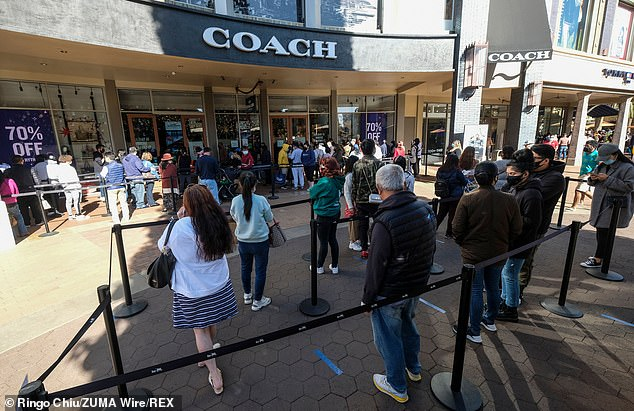 Shoppers wearing face masks line up to enter a Citadel Outlets store on Black Friday during the coronavirus pandemic in Commerce, Calif. (Pictured November 27)