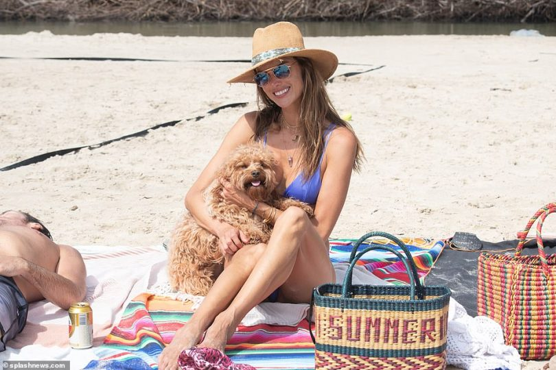 Picnic: She held her dog close as she and her family did some sunbathing on a colorful blanket