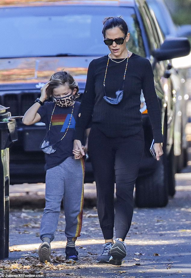Close: Jennifer Garner enjoyed a stroll around her LA neighborhood on Sunday with son Samuel, eight, and the two held hands as they walked along the leafy sidewalks