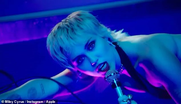 Miley Cyruswrithes around in a plunging black bodysuit as she belts the lyrics to Angels Like You