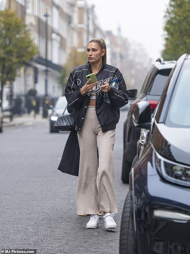 Sporty:Strolling along in simple white trainers, the reality star kept warm with the help of a navy baseball jacket