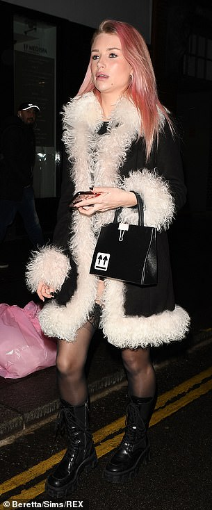 Turning heads: Cutting a typically chic figure, the influencer styled a black playsuit with a fluffy coat