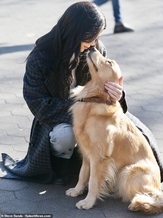 So sweet: She could be spotted falling into a squat to bring affection to her canine co-star, who appeared to be a golden retriever