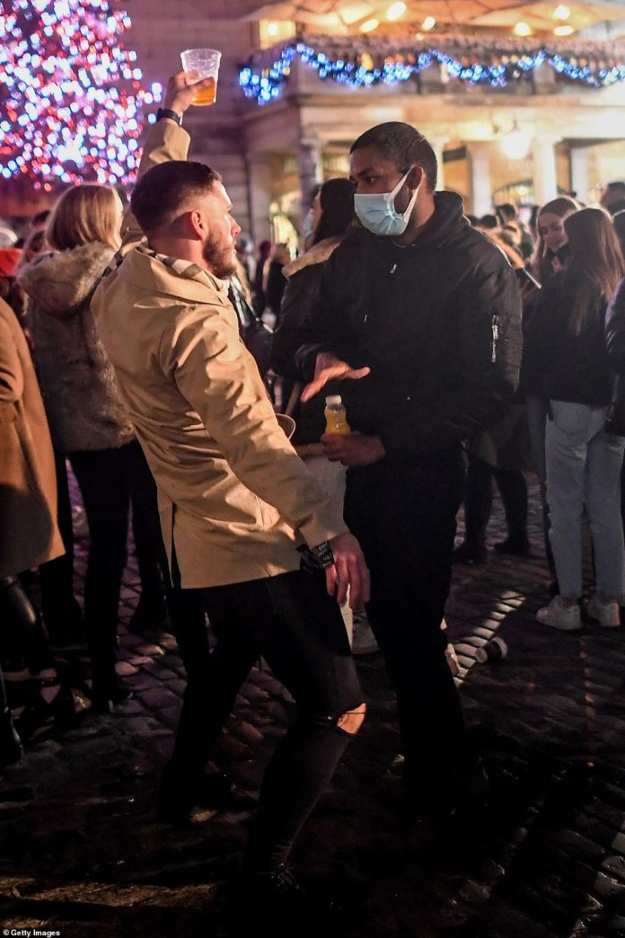 A man holding a pint dances in front of a man wearing a mask in Covent Garden, London's West End, on December 5