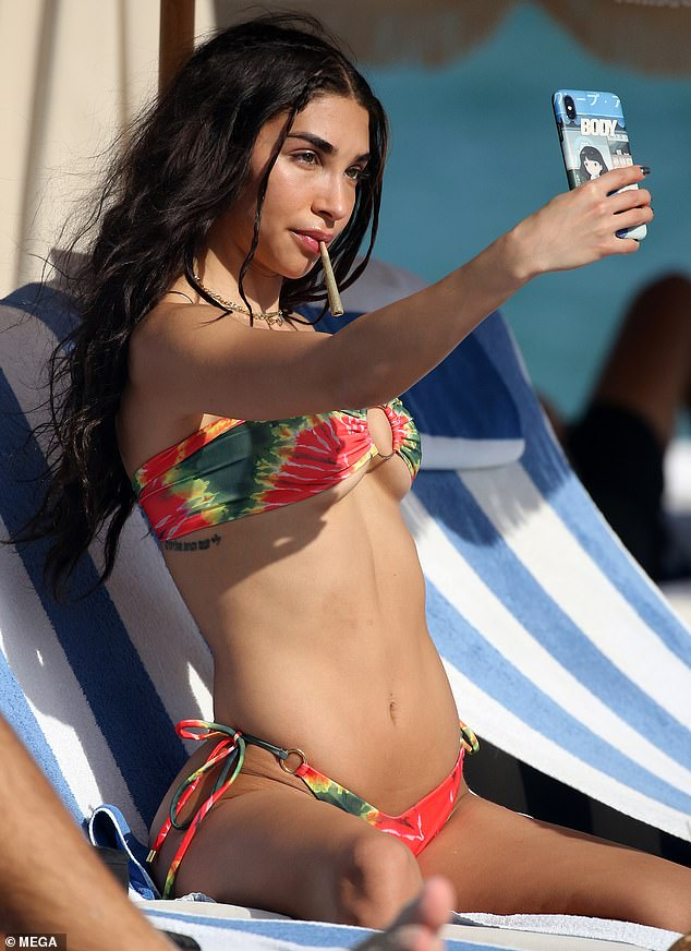 Chantel Jeffries puffs on a suspicious-looking cigarette on the beach
