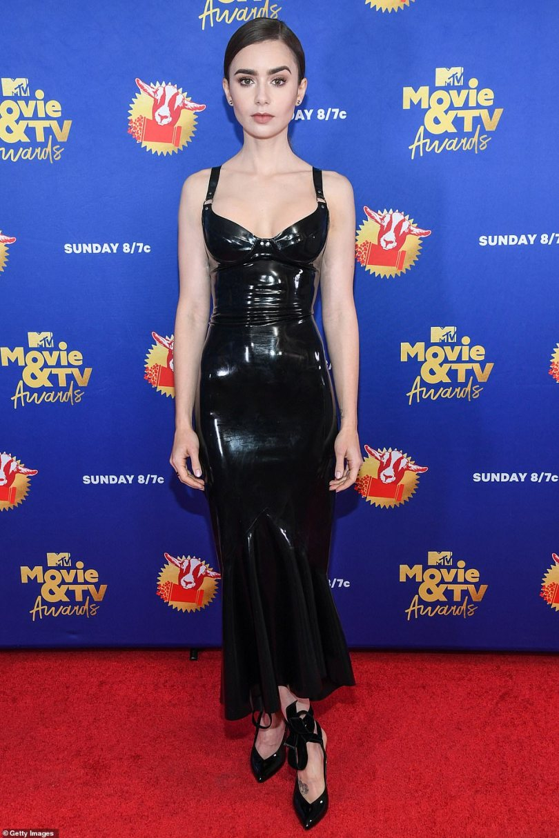 Lovely in latex: Lily Collins also opted for an edgier look for the night by donning a black latex mermaid dress that hugged every curve of her body