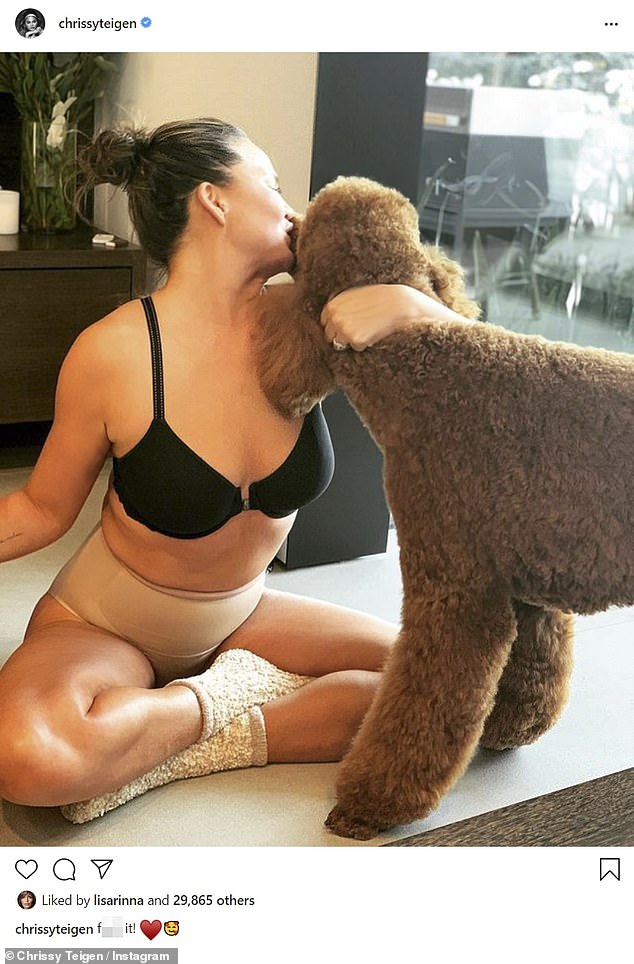 Not hiding: Chrissy Teigen, 35, said 'f**k it!' as she shared a photo of herself in underwear and fuzzy socks as she hugged her fluffy poodle Petey and planted a kiss on his snout