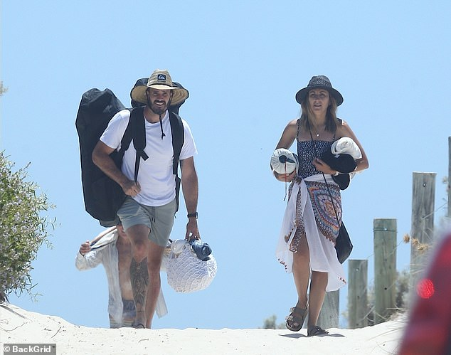 Beach adventures: The pair were seen carrying beach gear as they made their way to the shore