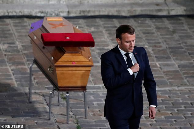 Pictured: French President Emmanuel Macron leaves after paying his respects by the coffin of slain teacher Samuel Paty. Justice Minister Eric Dupond-Moretti said the measure was inspired by the teacher's killing