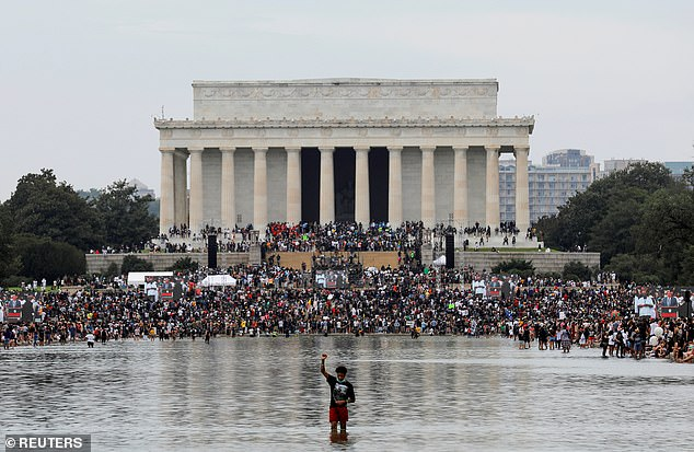"""A protester waves his fist as others gather outside the Lincoln Memorial for the """"Get Your Knee Off Our Necks"""" march for racial justice on August 28.  The protesters are also among the finalists for TIME Person of the Year"""