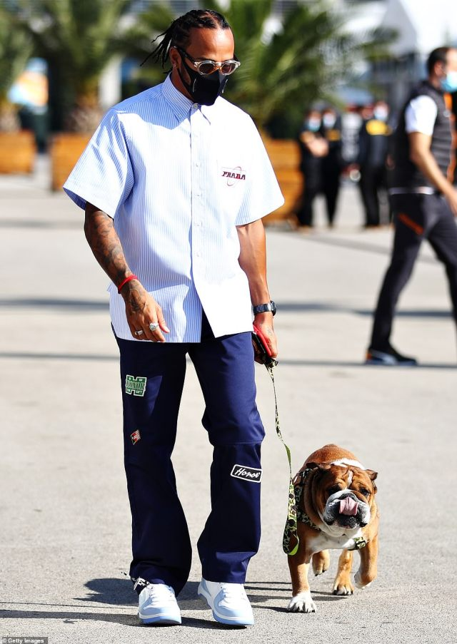 More designer labels were on display when Hamilton stepped out in a £510 pinstripe Prada shirt and £140 cargo pants to walk his dog Roscoe ahead of the Turkey Grand Prix. Both the shirt and trousers featured retro patches. The outfit was finished with a pair of trainers