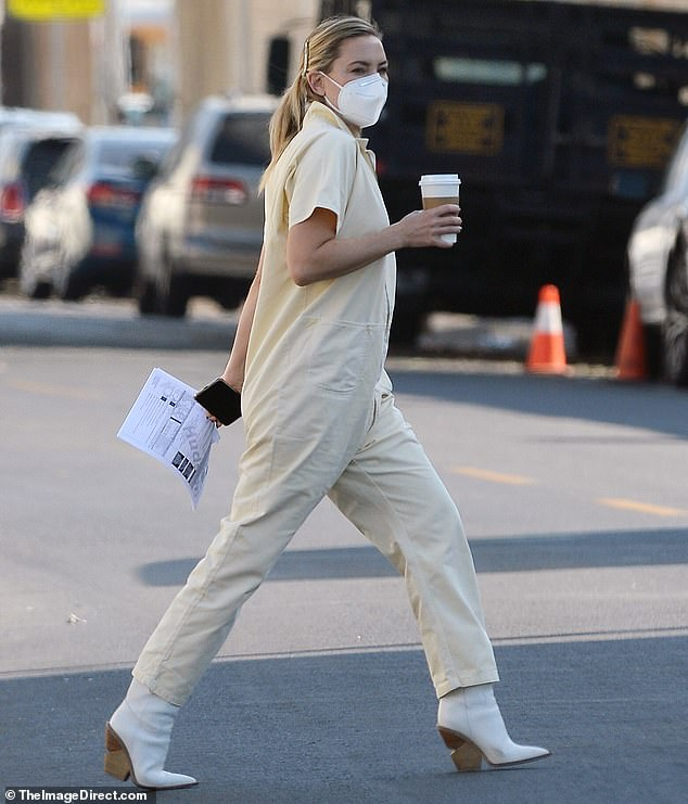 Stylish display: While the 41-year-old Golden Globe winner was first spotted sporting black slippers and a burgundy robe over a pair of tan trousers, she changed into a yellow jumpsuit with white booties