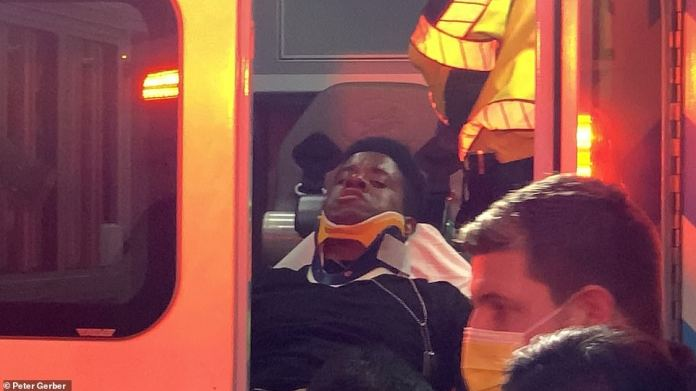 Injured man is seen in a neck brace in the back of an ambulance after the incident on Friday afternoon