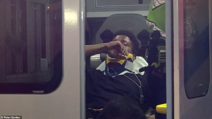 An injured protester sits in the back of an ambulance.  Several people were taken to hospital following the incident