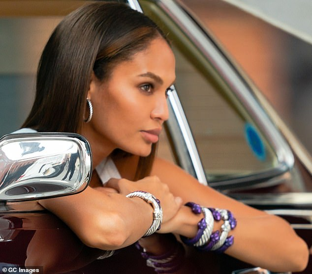 Making it happen:Joan could also be seen bedecked in silver and royal purple bracelets as she leaned out the window of a vintage car for an evocative set of snaps