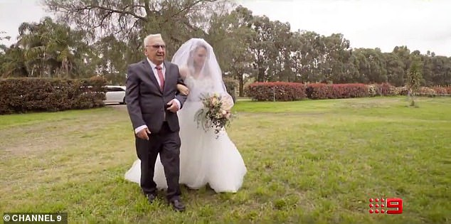 Hidden:Yet one more bride is covered up by a veil over her face as an older man walks her towards her husband-to-be