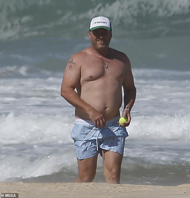 Having a ball: Karl appeared in good spirits during the sun-soaked outing, as he enjoyed cooling off in the water and playing a spot of beach cricket