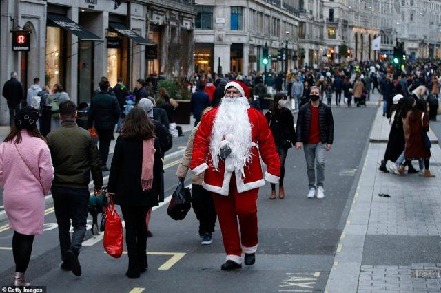 Experts have warned the Government is sending the 'wrong message' by only asking families to 'follow the rules', with some suggesting a third wave of infections could be sparked in the new year. Pictured: Shoppers, and a man dressed as Santa Claus, on Regent Street