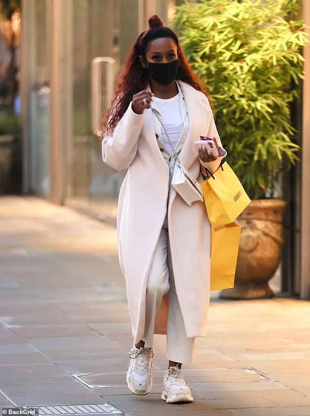 Chic: The singer, 32, nailed daytime glamour in a stylish cream suit and a white T-shirt, which she teamed with a chic oversized white jacket