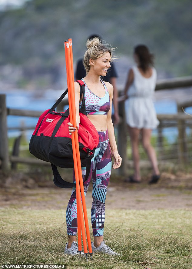 Ready for action:Wearing the heavy bag slung on her shoulder, she also held up a number of orange spiked poles