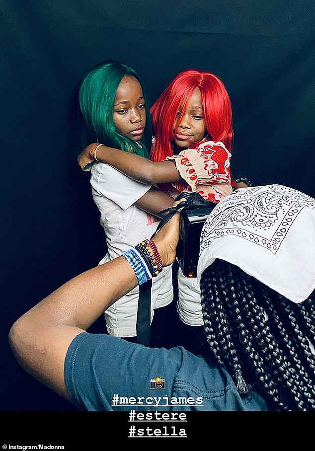 Sweet: The young duo shared a hug as they wore green and red hair extensions for the snaps by Mercy