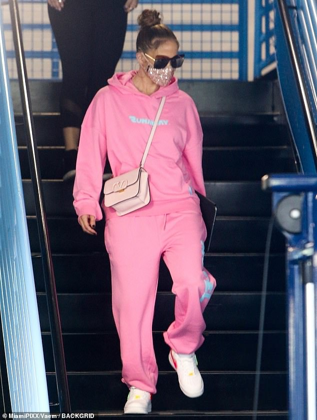 Colorful: Jennifer swapped her dark red outfit for a hot pink tracksuit.  She completed it with a pale pink Valentino handbag and shiny white Nikes with red and neon green swooshes.