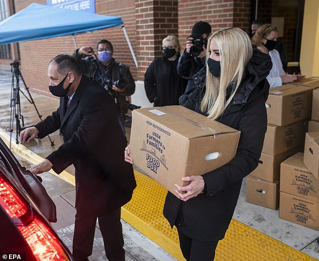 Support system: After loading up the boxes of food, Ivanka then helped to deliver them to families in the area