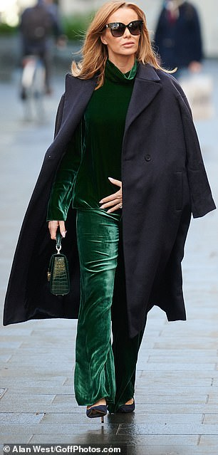Winter ready: Amanda looked poised as she held her emerald top down and embraced the cool December weather