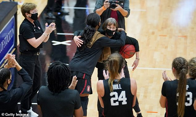 Head coach Tara VanDerveer of the Stanford Cardinal is congratulated by her team after she sets the record for the most victories in Division I women's basketball, with 1,099 during a game between Stanford and Pacific at Alex G. Spanos Center on December 15 in Stockton
