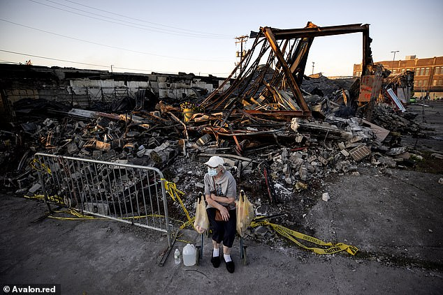 Sandra King, 70, waits for her granddaughter near the remains of a burned-out AutoZone across from the Minneapolis Third Police Precinct on May 28