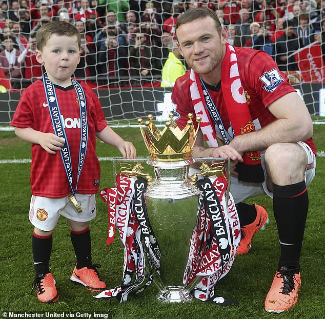 Rooney poses alongside his son Kai with the Premier League trophy in May 2013