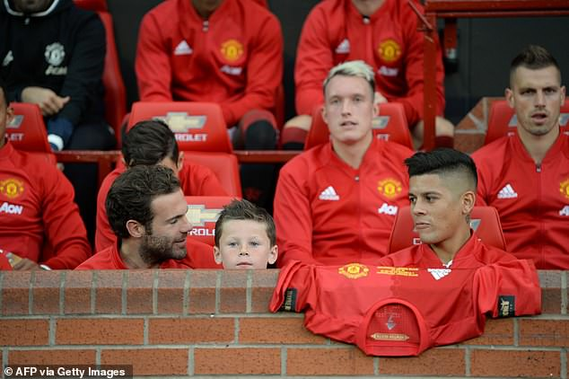 Kai sits in between Juan Mata and Marcos Rojo on the United bench in August 2016
