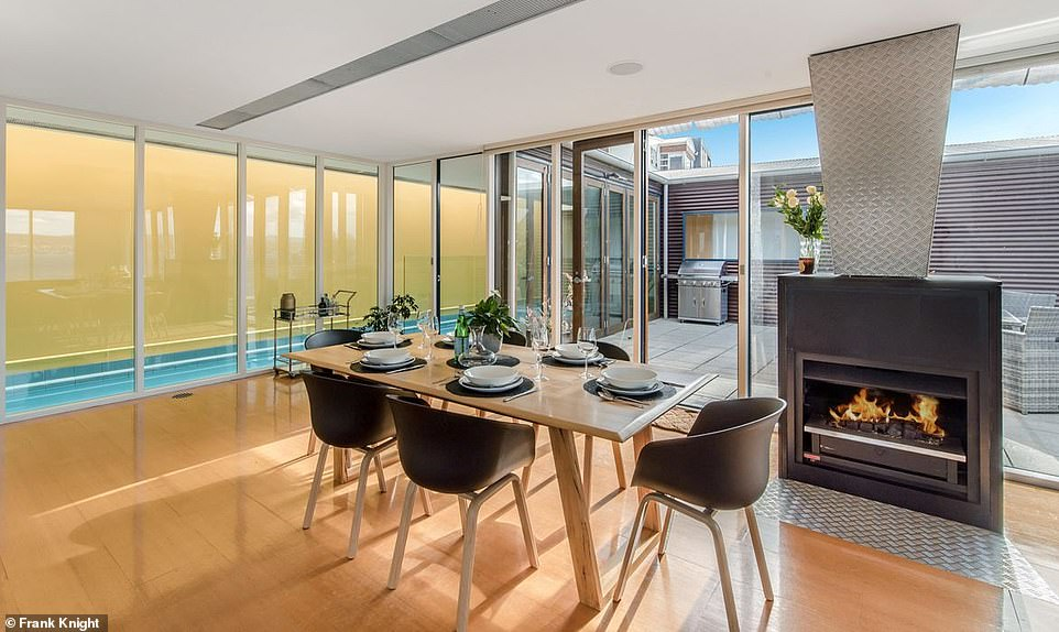 The walkway from the pool leads to an expansive and light-filled kitchen and dining area, which includes a modern gas fireplace (pictured)