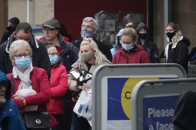 People were seen in masks as they waited in line outside the Tesco store in Cirencester this morning