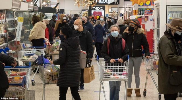 Crowds of shoppers were seen in a Tesco Extra store in south east London today as people flocked to supermarkets days before Christmas