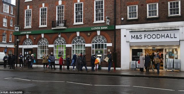 People queue to get inside a Marks and Spencer branch in North London for their Christmas food shopping this afternoon