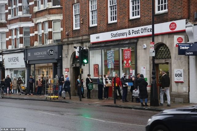 People queue outside a Post Office in North London this afternoon as they send some last-minute packages