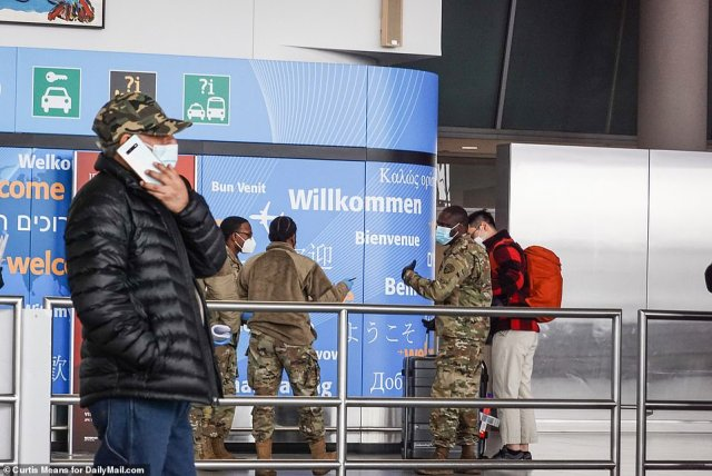 National Guard screen people at JFK airport on Dec 21 2020 as passengers arrive from overseas. It's unclear what they were asking them. The state law in NY is that people arriving from other states test negative 72 hours within arriving, quarantine for three days and then test negative again on the fourth day. The CDC guidance for people coming from overseas is that they quarantine for 14 days, if they can get into the country at all