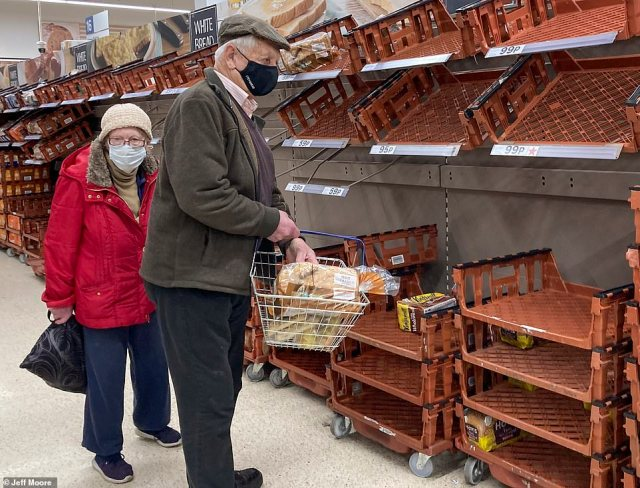 This elderly couple at a Tesco store in east London look at the empty shelves this morning after many headed to the shops to stock up for Christmas